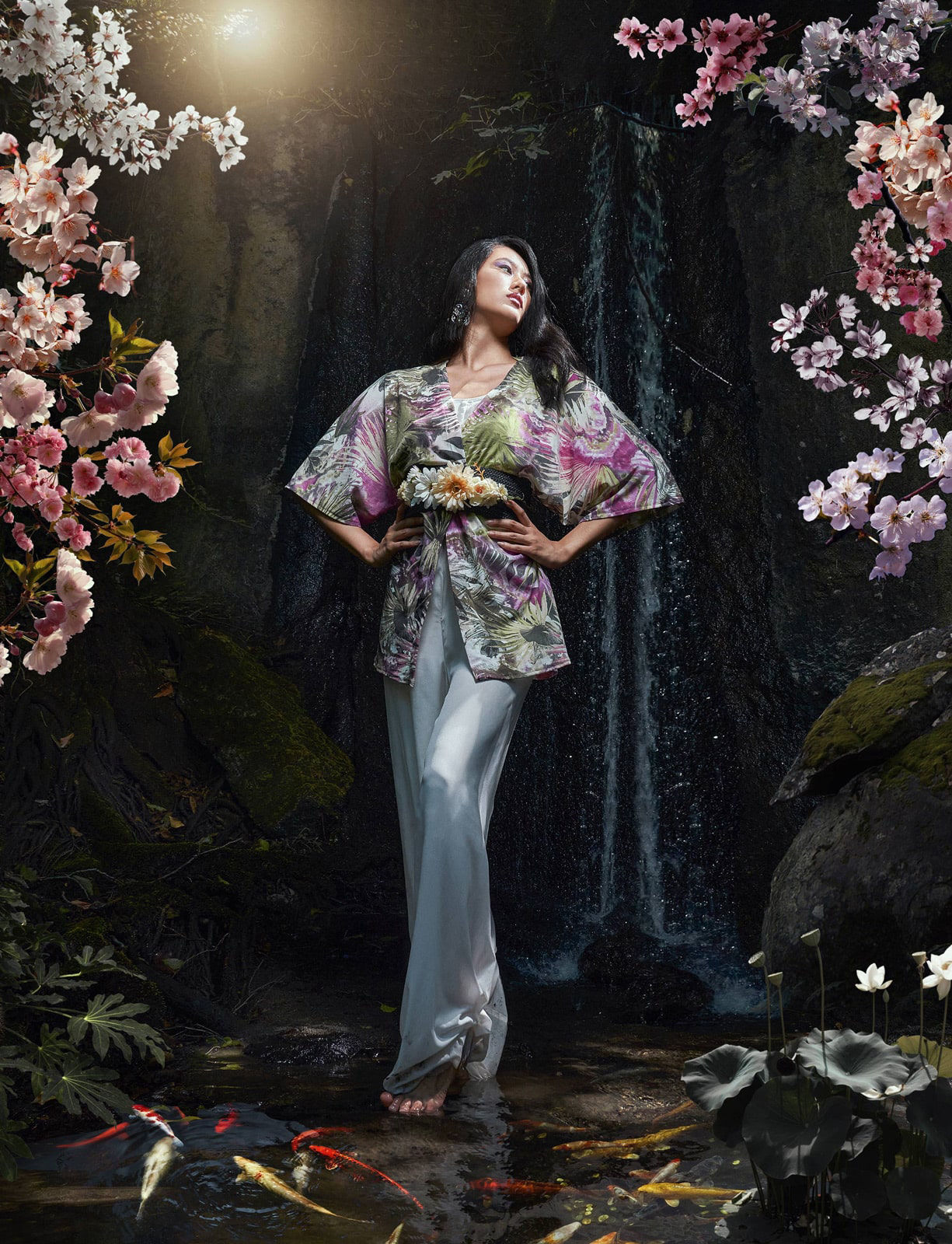 fashion photography of a cinese model wearing a kimono posing in nature with waterfalls and cherryblooms